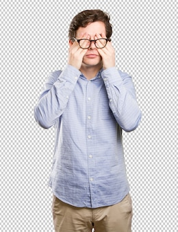 Frightened young man covering his eyes