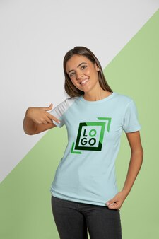 Front view of woman pointing at the t-shirt she's wearing