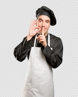 Happy young chef doing a silence gesture