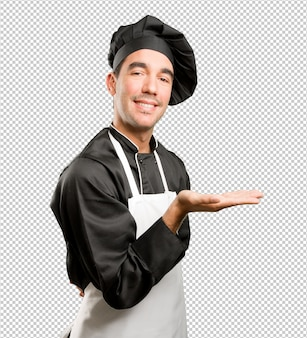 Happy young chef with a hold gesture
