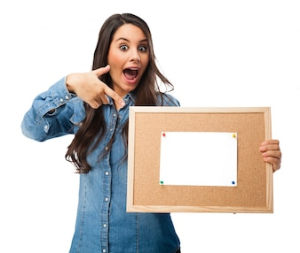 Joyful teenager pointing to a cork board with a blank paper