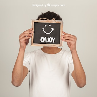 Man holding slate in front of face