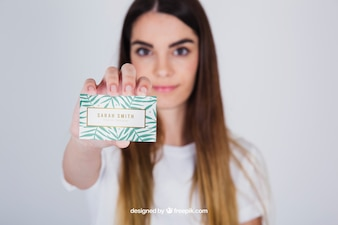 Mockup concept of young woman presenting business card