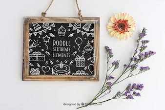 Mockup design with birthday slate and floral decoration