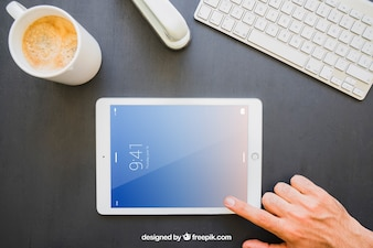 Office desk and finger touching horizontal tablet