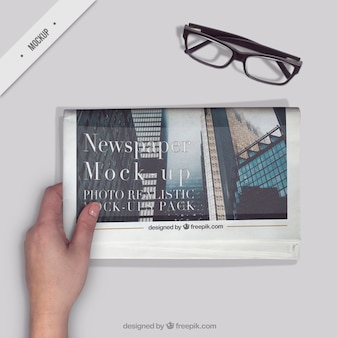 Person reading a newspaper with a glasses on the desktop
