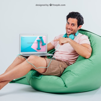 Smiley young guy pointing laptop's mock up