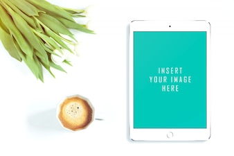 Tablet on white background with flowers and coffee mock up
