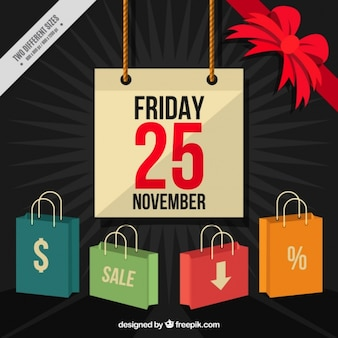 Background for black friday with colorful shopping bags and a red bow
