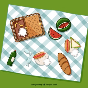 Basket with picnic elements and food in top view