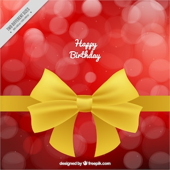 Birthday background with golden ribbon and bokeh effect