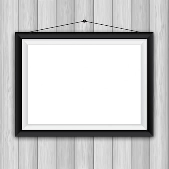 Blank picture frame on a wooden wall background