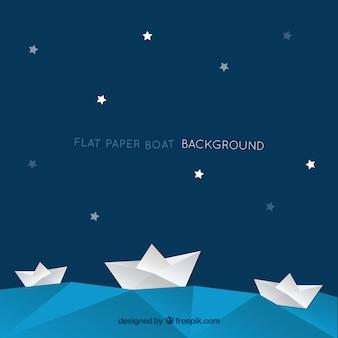 星と紙ボートを持つ青い背景