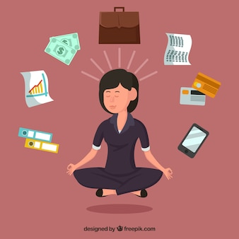 Businesswoman meditating surrounded by objects