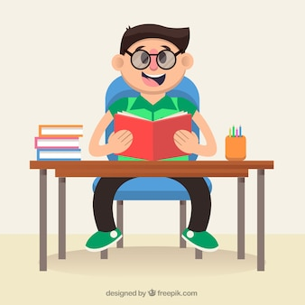 Cheerful child sitting at his desk and reading