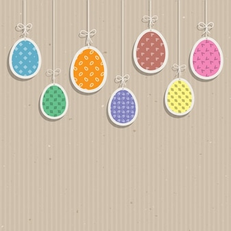 Cute Easter eggs hanging against a cardboard texture