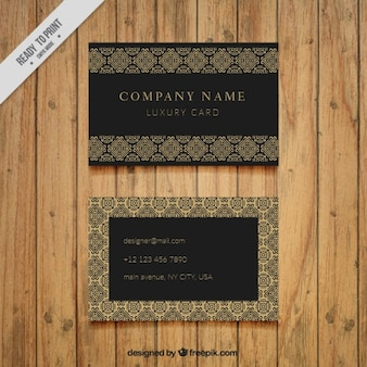 Dark business card with golden ornaments