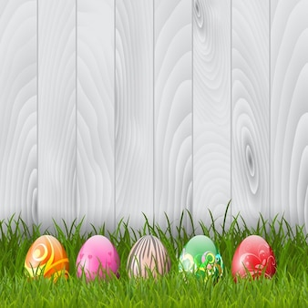 Decorative Easter eggs in grass on a wood background