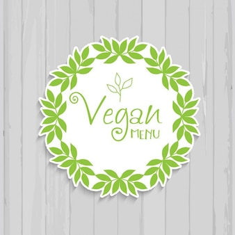 Decorative vegan badge on a wooden background