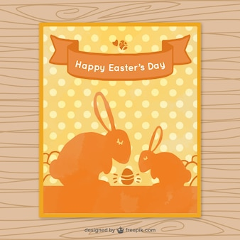 Easter greeting card with orange rabbits