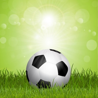 Football background with soccer ball in grass
