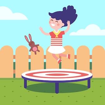 裏庭でトランポリンにジャンプする少女