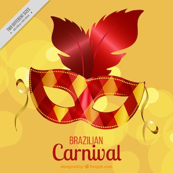 Golden background of elegant carnival mask with feathers