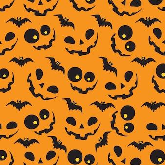 オレンジ色のカボチャとコウモリとハロウィーンのパターン