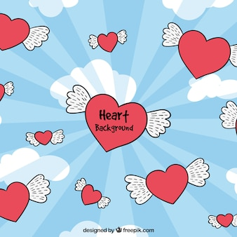 Hand drawn hearts with wings sky background