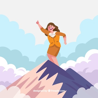 Happy businesswoman on the top of a mountain