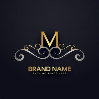 M логотип с золотыми украшениями