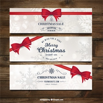 Merry christmas banners with red ribbons and snowflakes