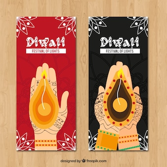 Pretty diwali banners of hands with candles