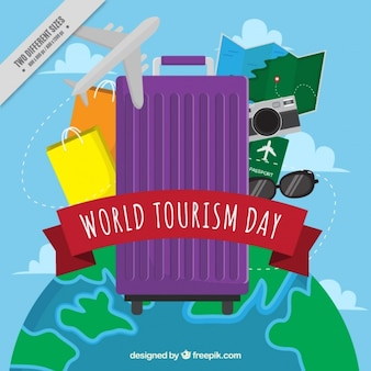 Purple suitcase with other items for tourism day