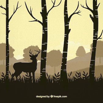 Reindeer between trees silhouettes background