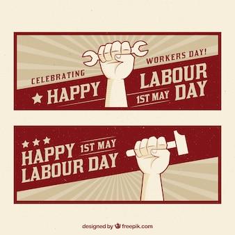 労働者の日のためのツールを保持している手でレトロなバナー