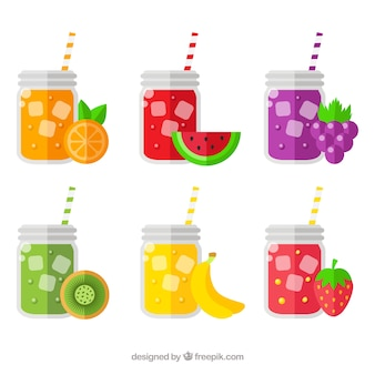 Selection of six glasses with fruit juices and straws