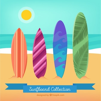 Several colores surfboards on the beach