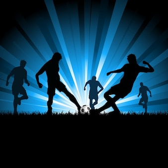 Silhouettes of men playing soccer
