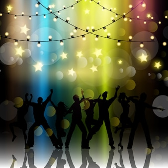 Silhouettes of people dancing on a bokeh lights background