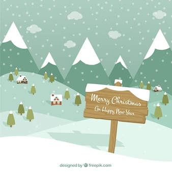 Snowy village landscape with mountains and happy christmas and new year sign