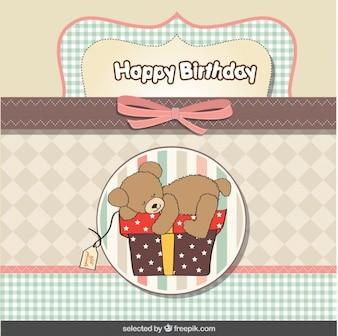 Teddy bear on present birthday card in pastel colors