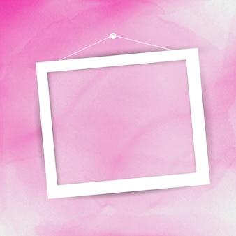 ピンクの水彩画の背景に掛かって空白の額縁