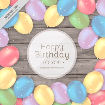 Wooden background with colored birthday balloons