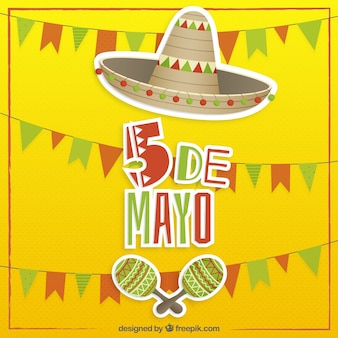 Yellow background of May five with a mexican hat and maraca