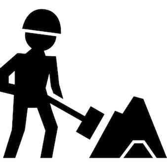 Werknemer van de bouw werken met een schop naast materiaal stapel