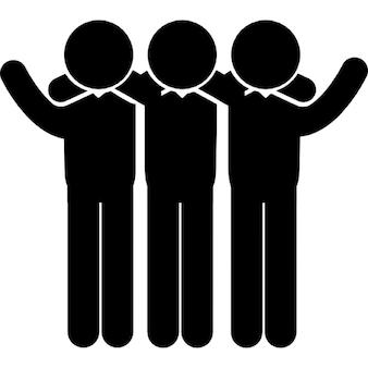 Grupo de três homens de pé, lado a lado, abraçando