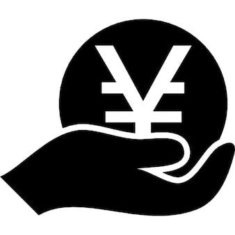 Mão segurando uma moeda yen japonês