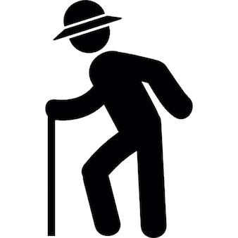 Anciano con sombrero de pie con un palo