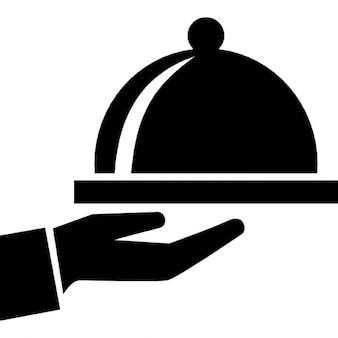 Bandeja de comida cubierta en una mano del servicio de habitaciones del hotel